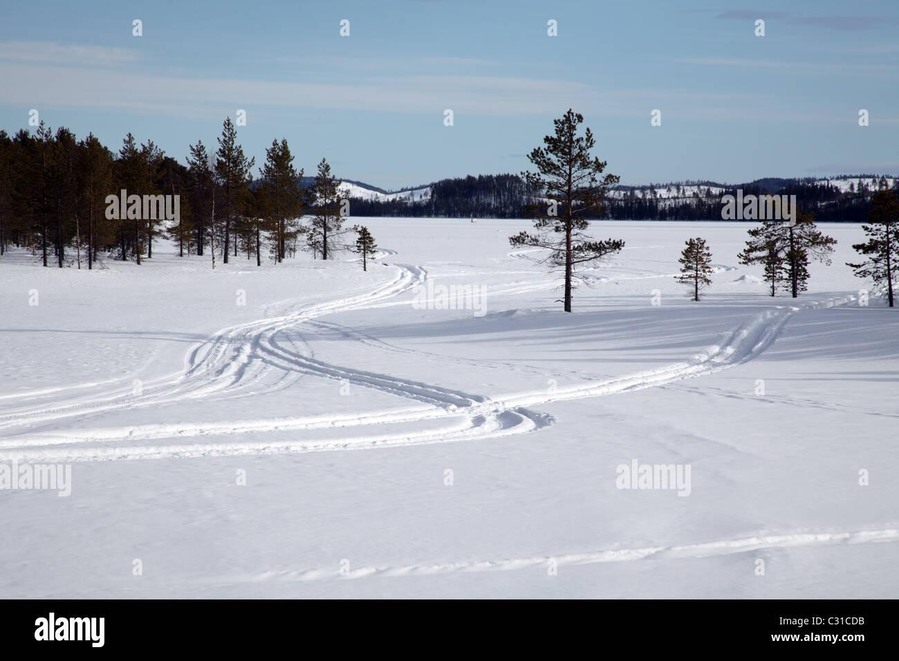 Snowmobile tracks across a frozen lake near Arvidsjaur, Northern Sweden - Stock Image