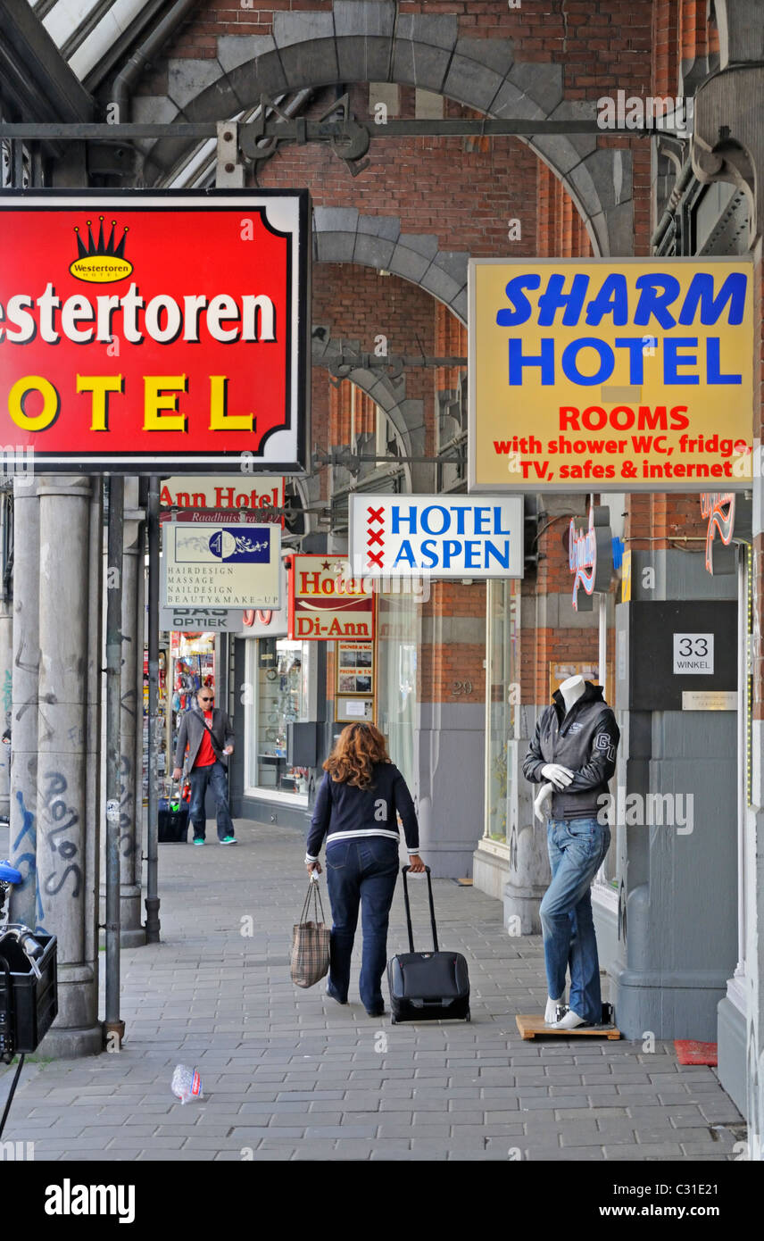 Amsterdam, Netherlands. Woman with luggage passing many hotel signs - Stock Image