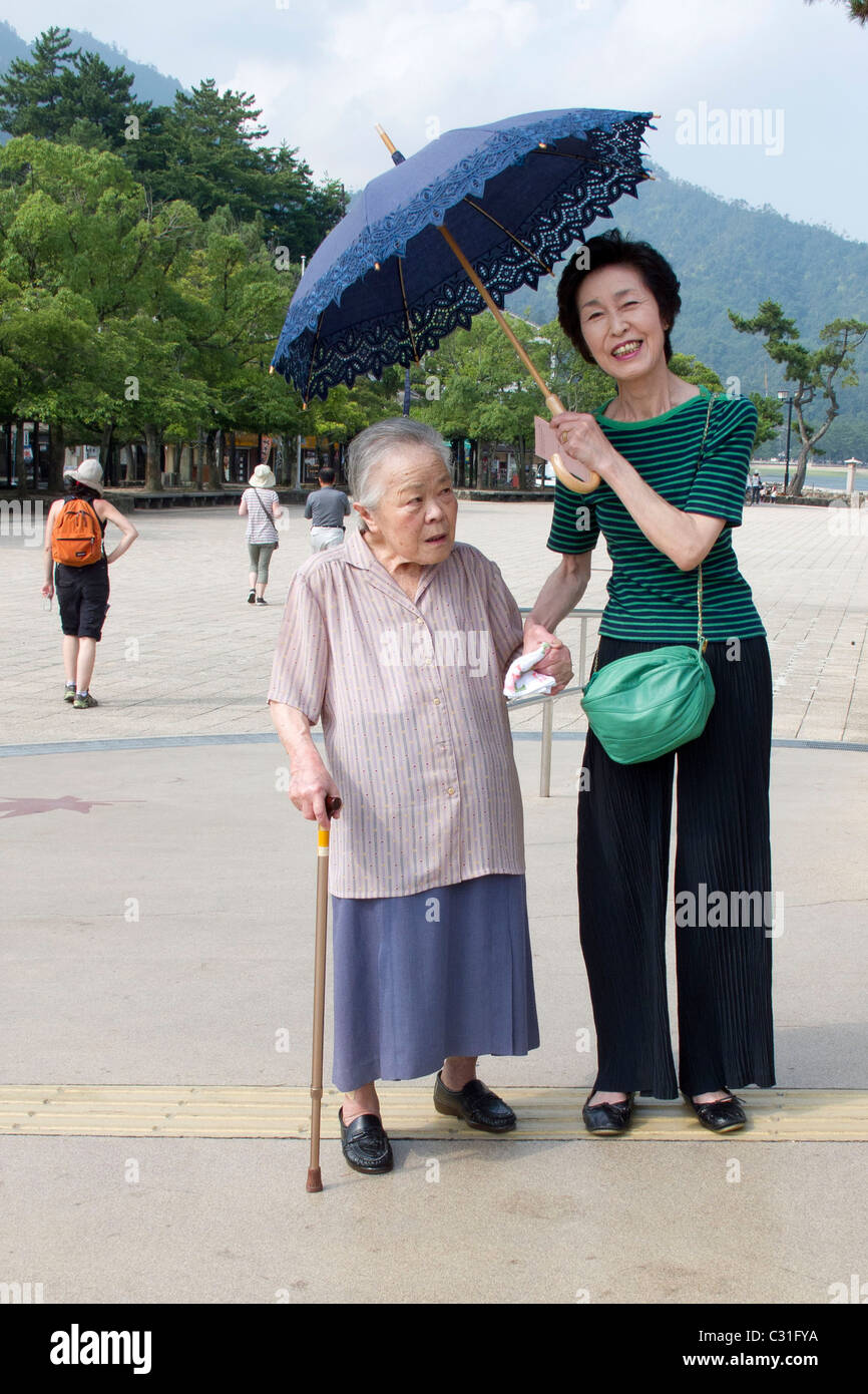 JAPANESE WOMEN ON MIYAJIMA ISLAND PROTECTING THEMSELVES FROM THE SUN WITH AN UMBRELLA, JAPAN Stock Photo
