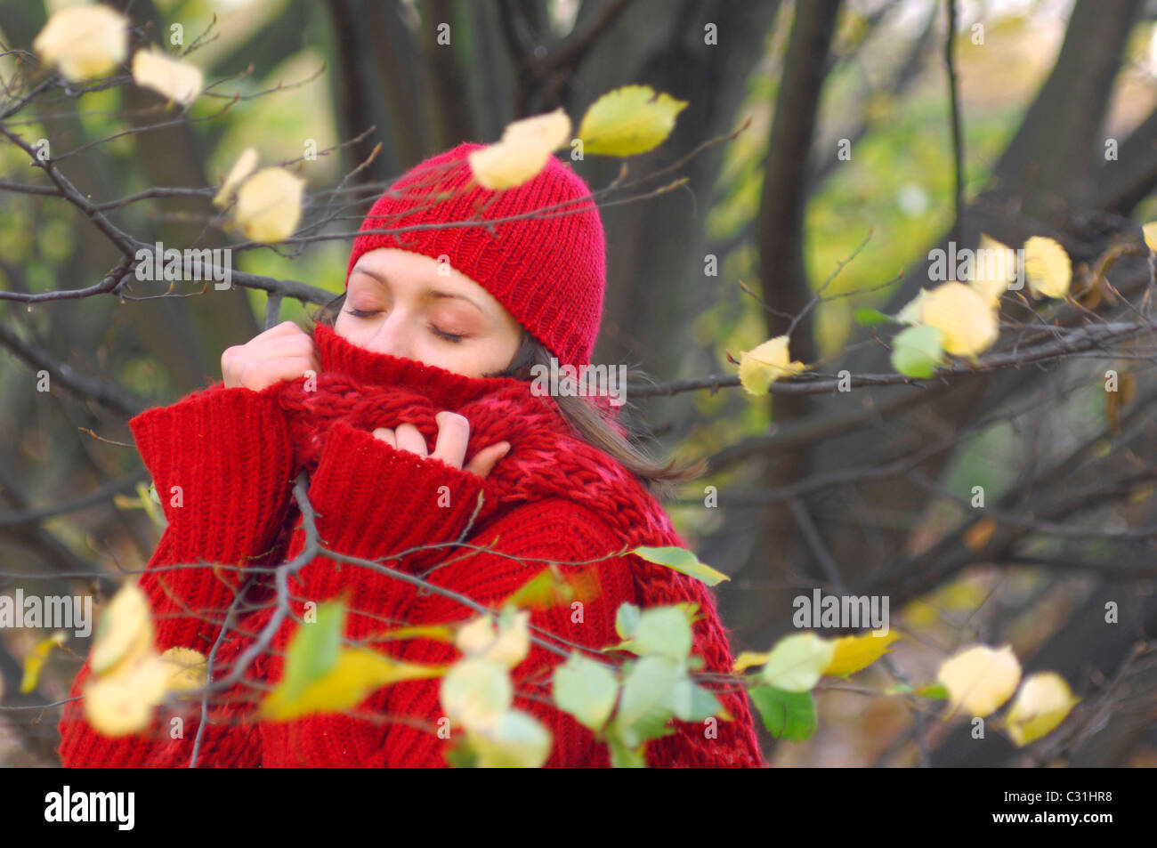 ALL MUFFLED UP, A YOUNG WOMAN REGENERATES HERSELF IN THE FOREST IN AUTUMN - Stock Image