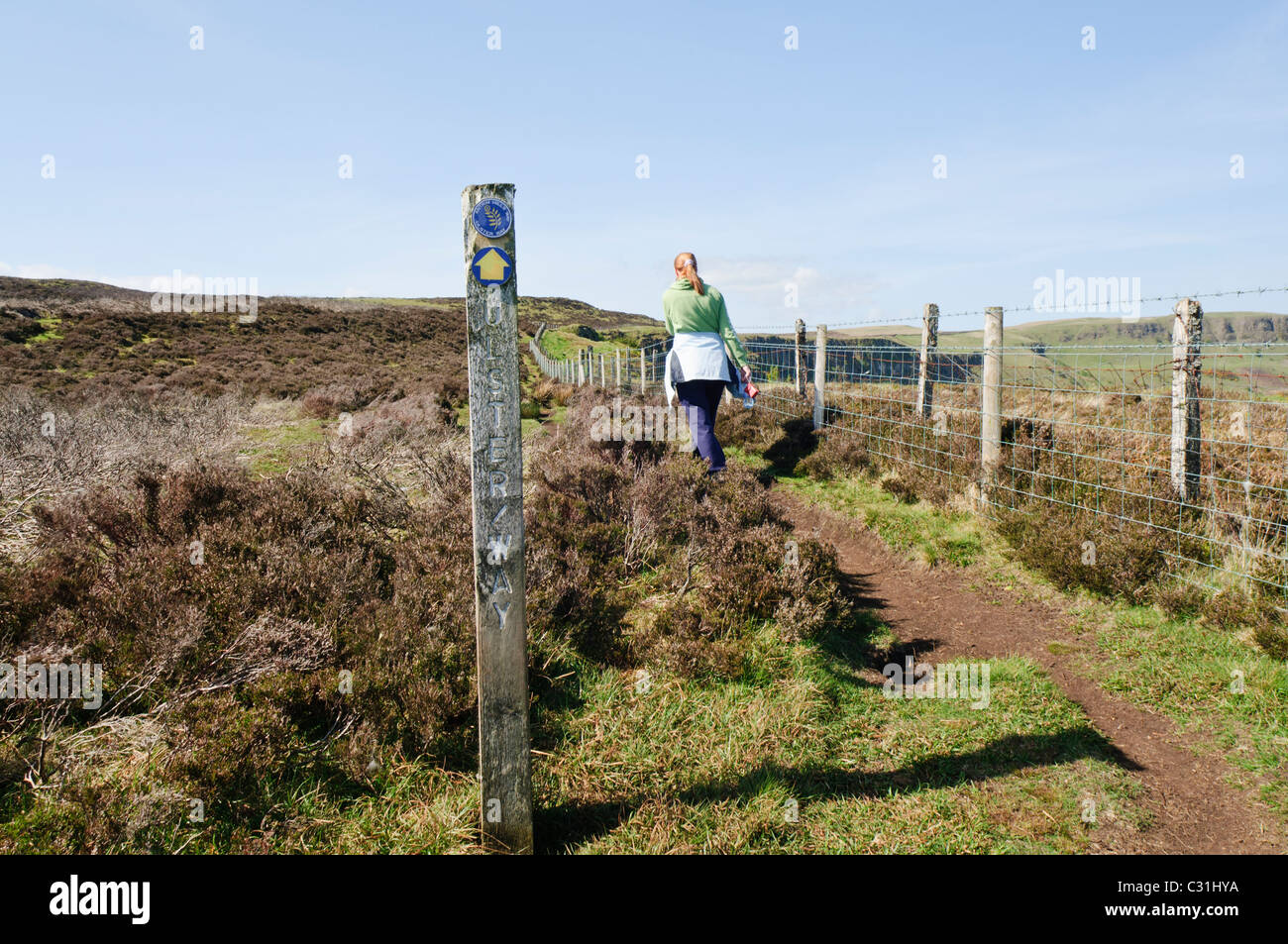 Woman walks past a direction sign post on the Antrim Hills Way, part of the Ulster Way - Stock Image