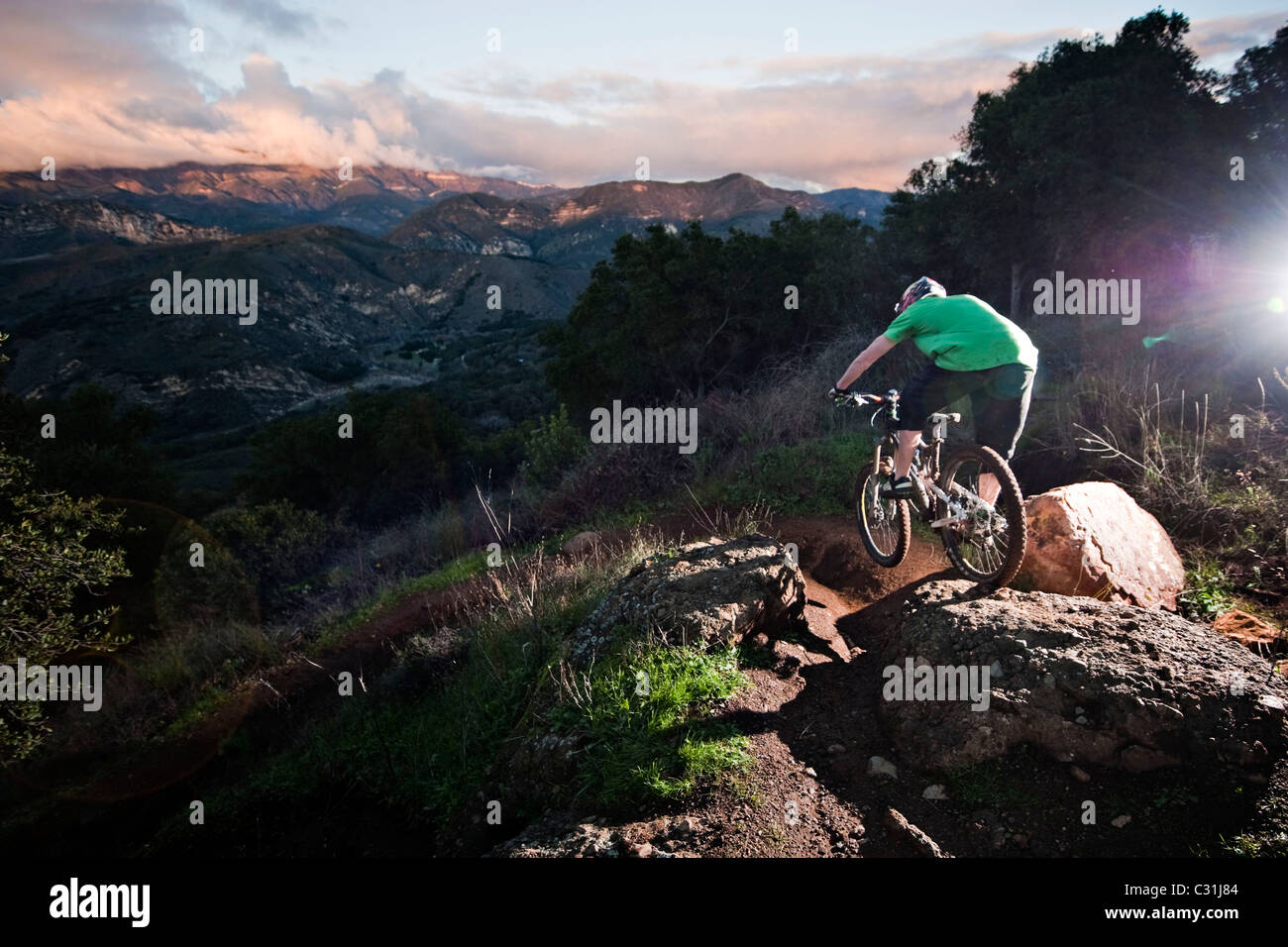 A young man rides his downhill mountain bike on Knapps Castle Trail, surrounded by beautiful scenery in Santa Barbara, - Stock Image