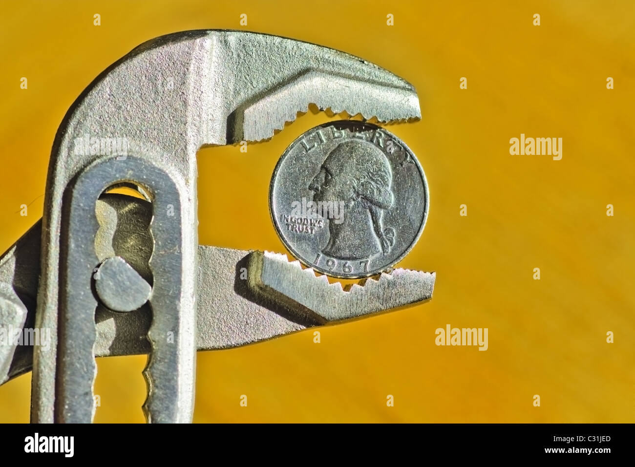Close up of an Dollar Coin between pliers, concept of financial crisis - Stock Image