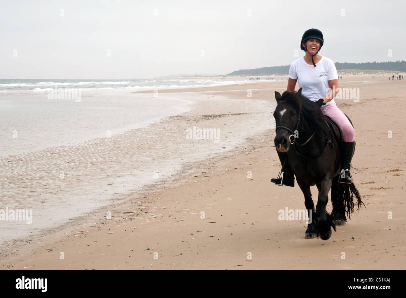 Girl riding her horse on Holkham Beach, North Norfolk, UK - Stock Image