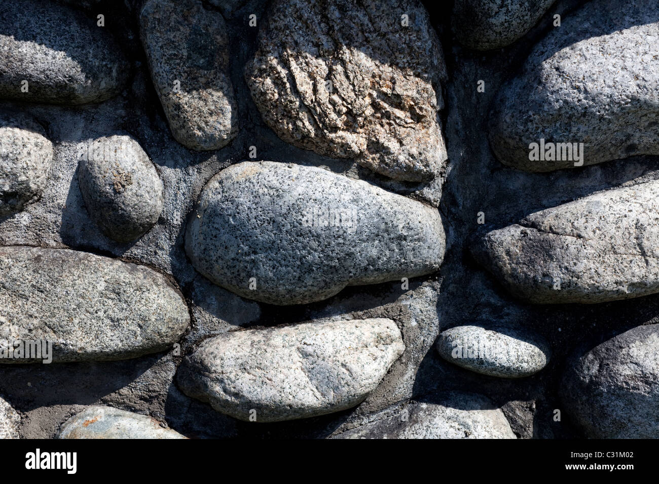 rounded river rocks wall for background - Stock Image