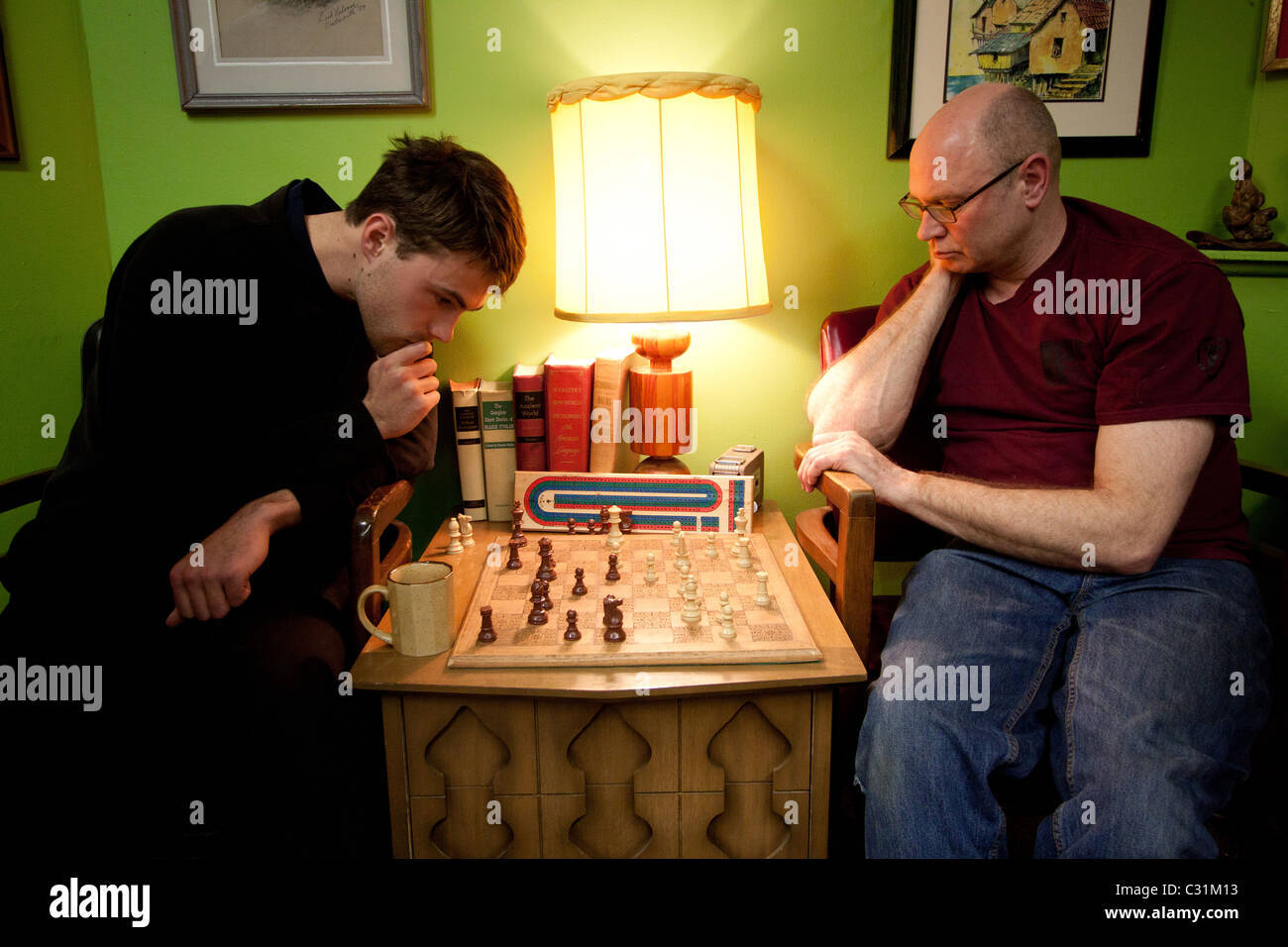 Two men play chess inside a barber shop. - Stock Image