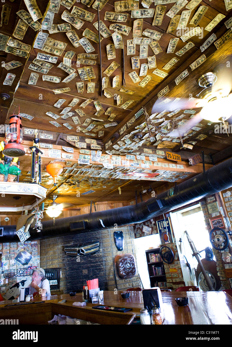 Signed one dollar bills tacked on the ceiling and walls of western bar - Stock Image