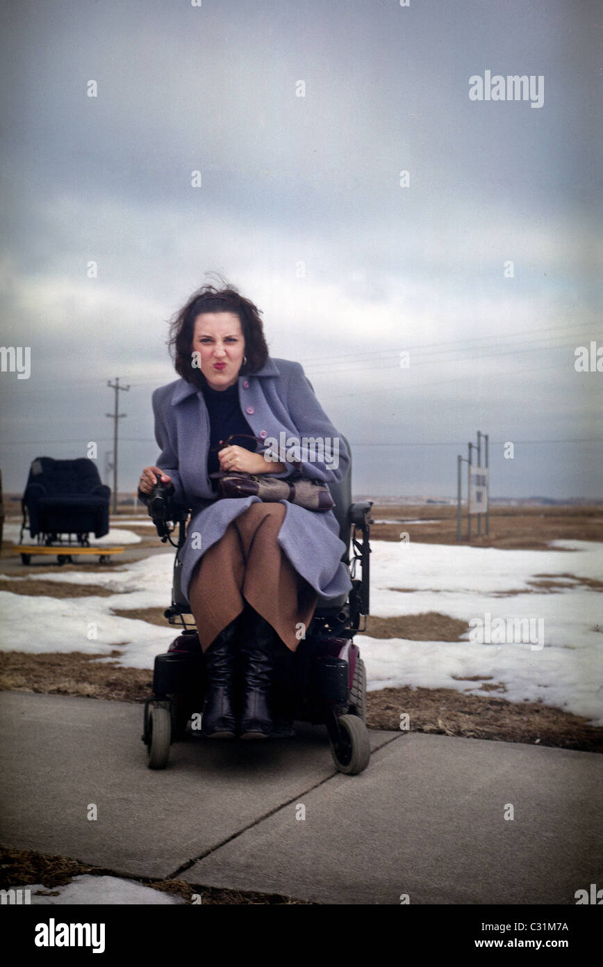 A young woman looks grumpy as she sits in a motorized wheelchair. - Stock Image
