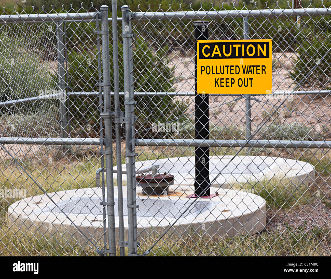 Caution polluted water sign on fence around water supply Big Bend National Park Texas USA - Stock Image