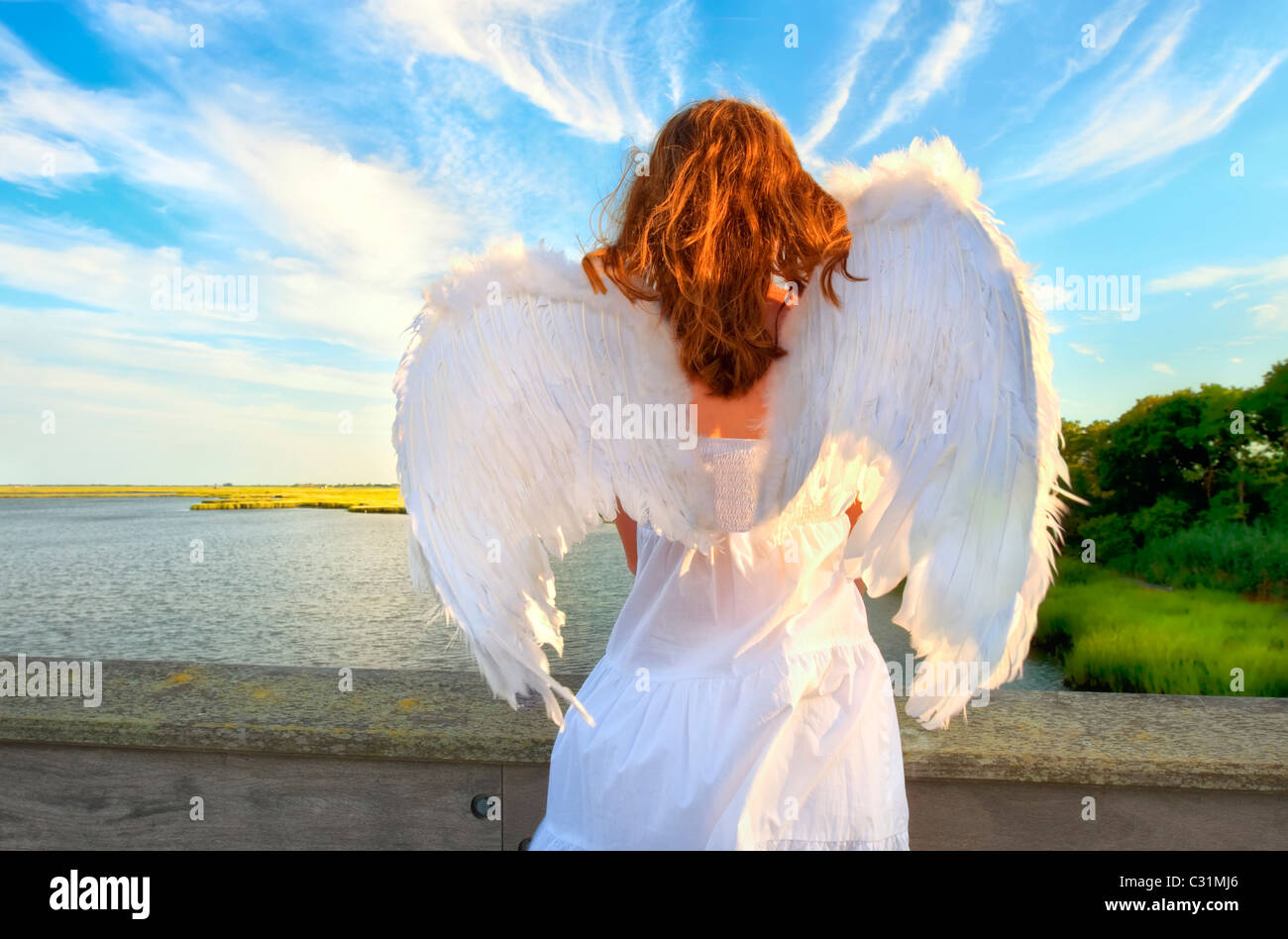 Guardian Angel young woman, from back, dusk at marsh bay - Stock Image