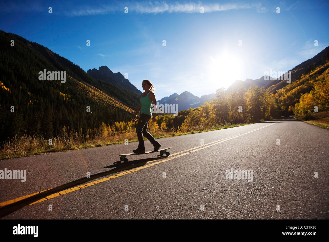 A young woman longboards down a smooth country road through the mountain peaks and gold forests. - Stock Image