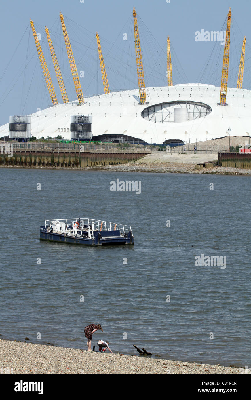 UK. RESIDENTS OF THE ISLE OF DOGS  BY THE THAMES IN LONDON ENJOY SUNSHINE, WITH MILLENNIUM DOME IN BACKGROUND - Stock Image
