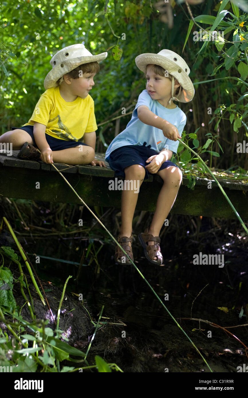 Five-year-old and three-year-old brothers pretend to fish - Stock Image