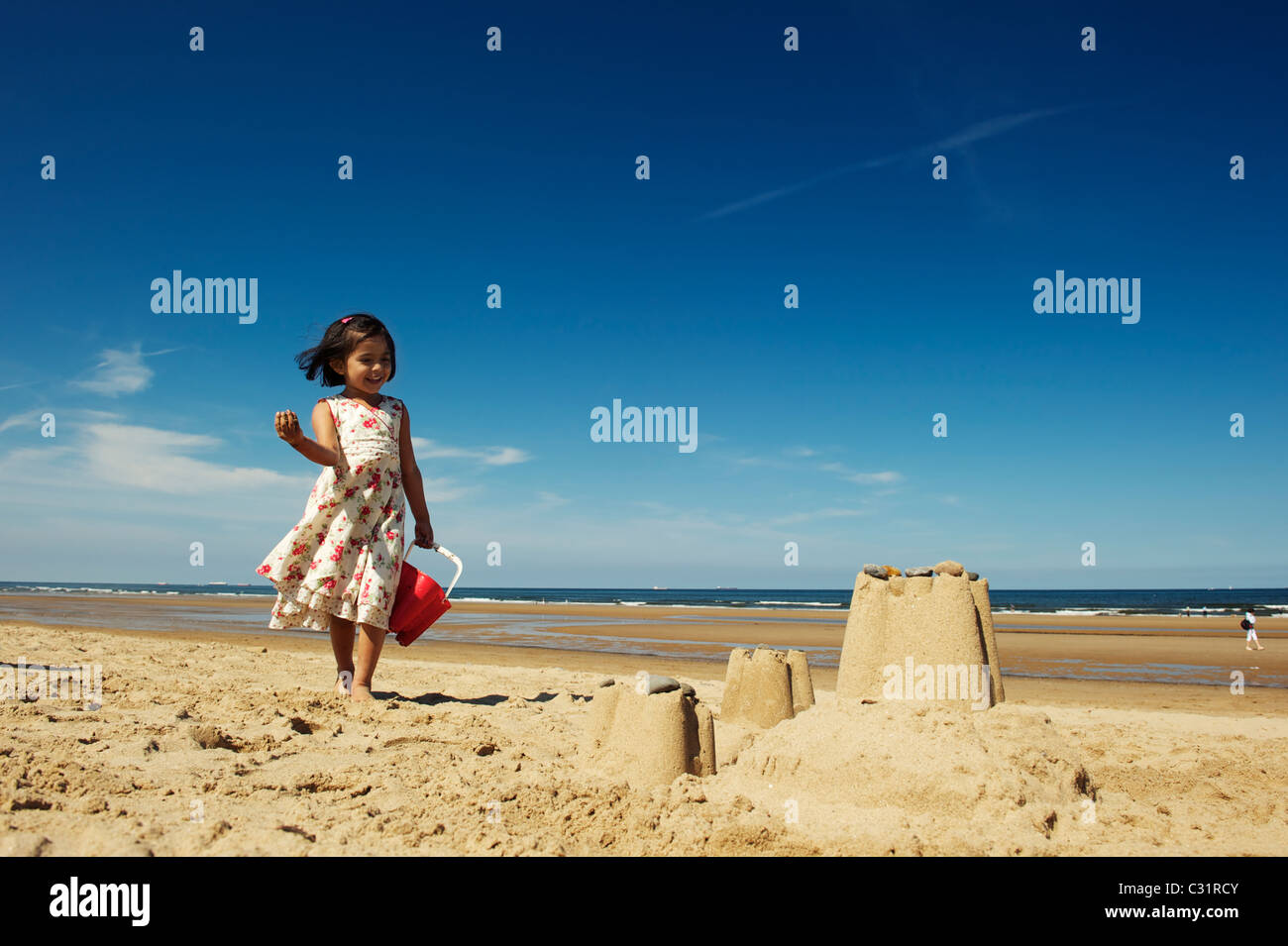 A young girl enjoy her sandcastle, Redcar Beach UK - Stock Image