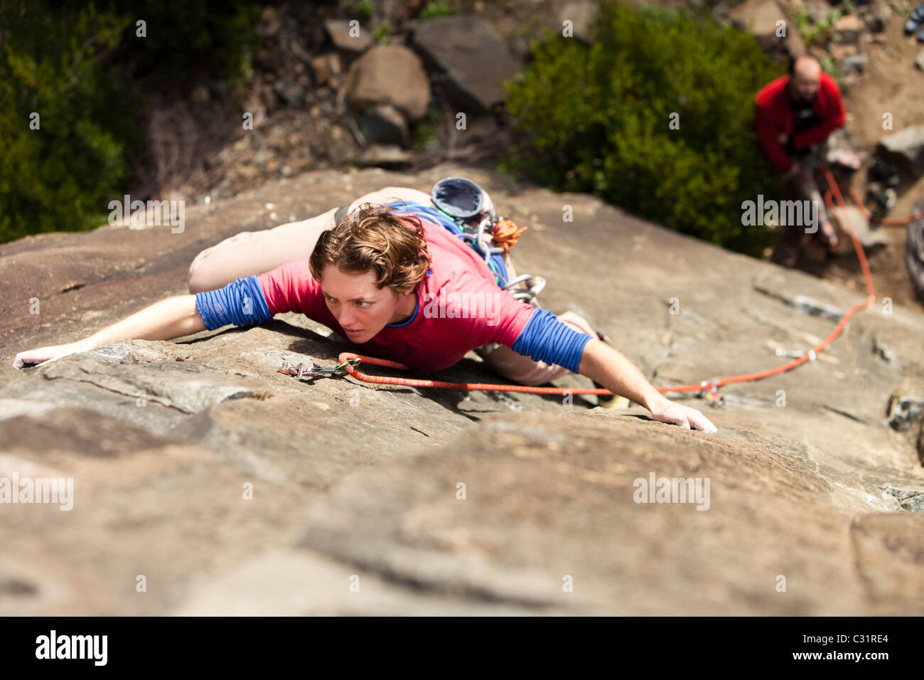An adult female climber shows her game-face on a route in Australia. - Stock Image