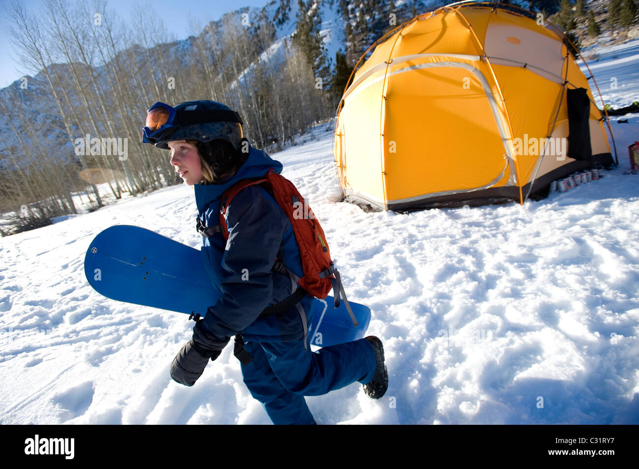 A boy gets ready to snowboard in the California backcountry. - Stock Image