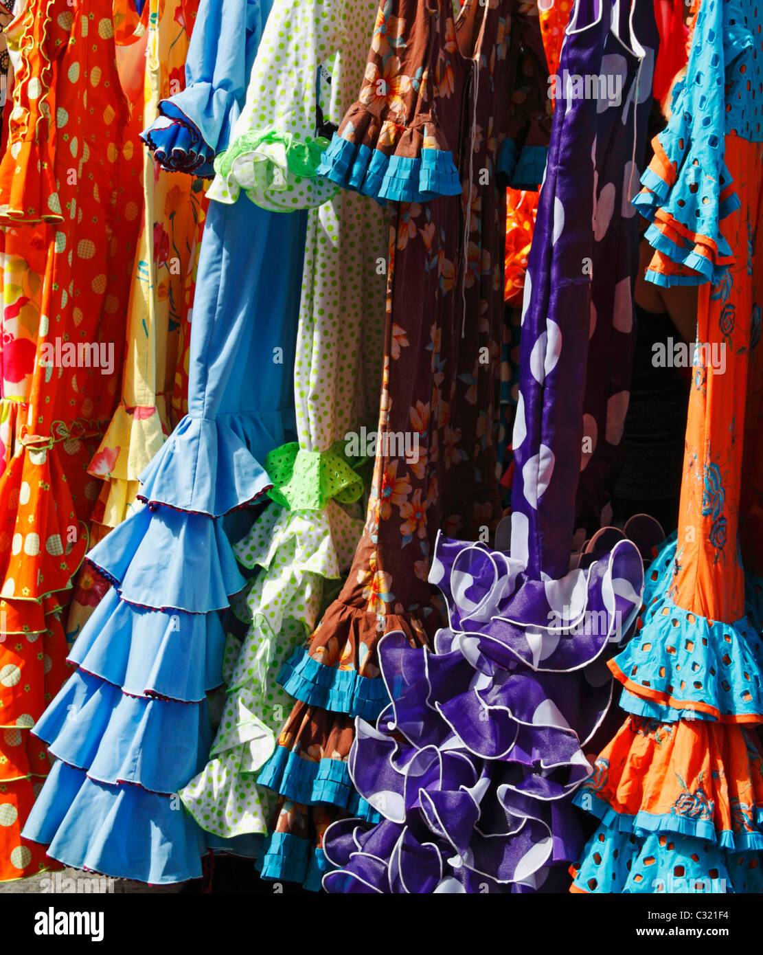 Flamenco dresses on market stall on famous street market in calle Feria, Barrio Macarena, Seville, Spain, Europe - Stock Image