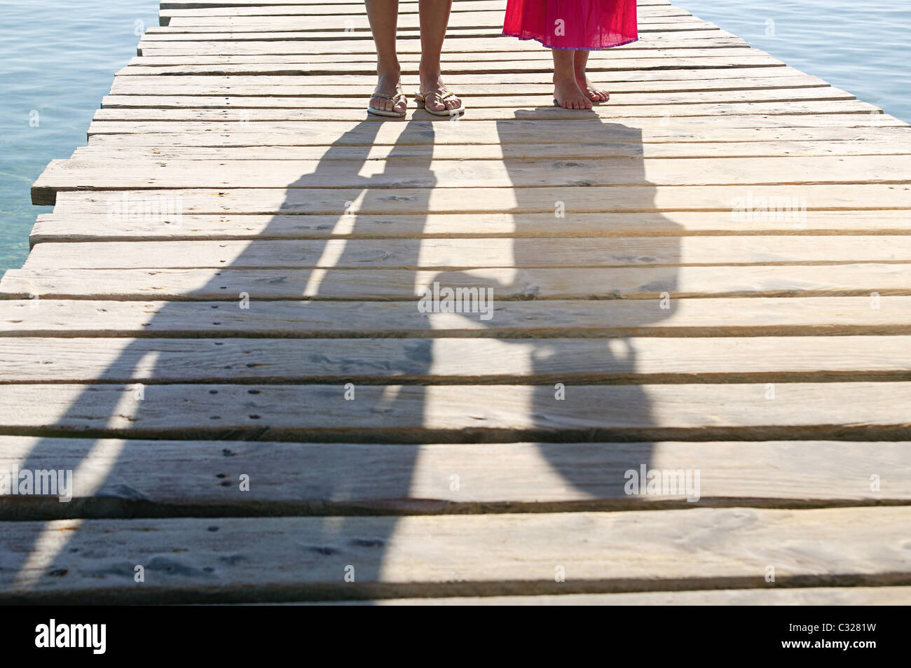 Shadows of child and adult on jetty - Stock Image