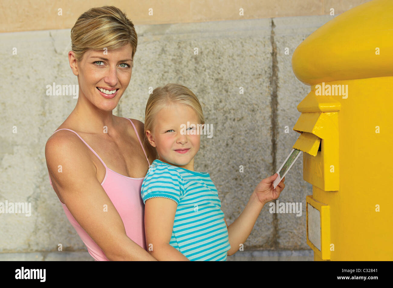 Mother and daughter at postbox - Stock Image