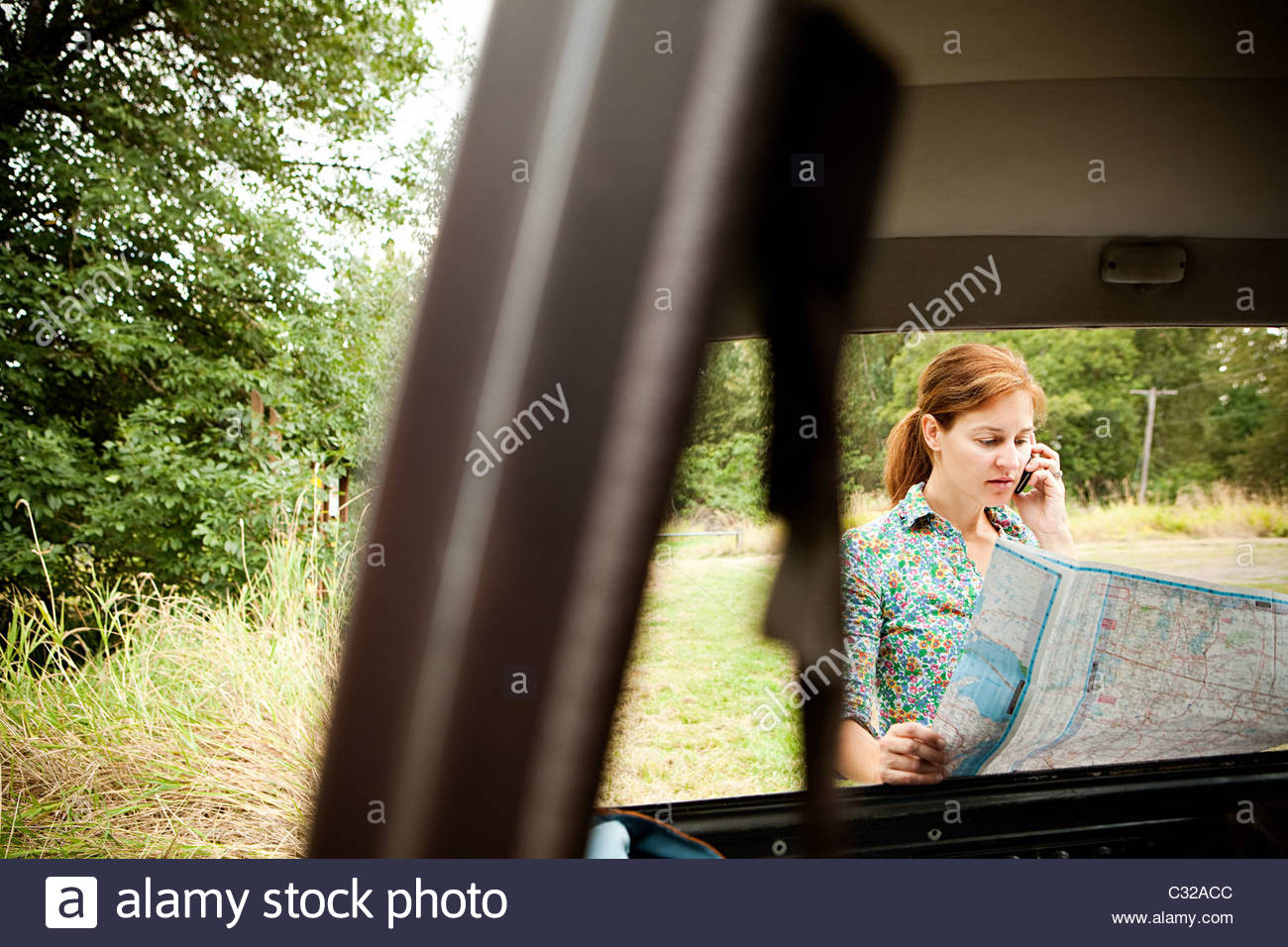 Woman using cellphone and map, viewed through a car - Stock Image