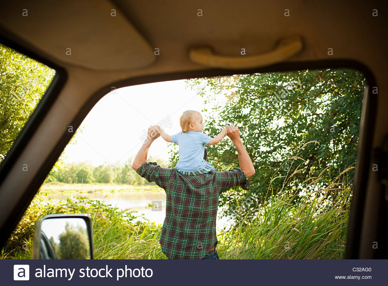 Father with son on shoulders, viewed from a car - Stock Image