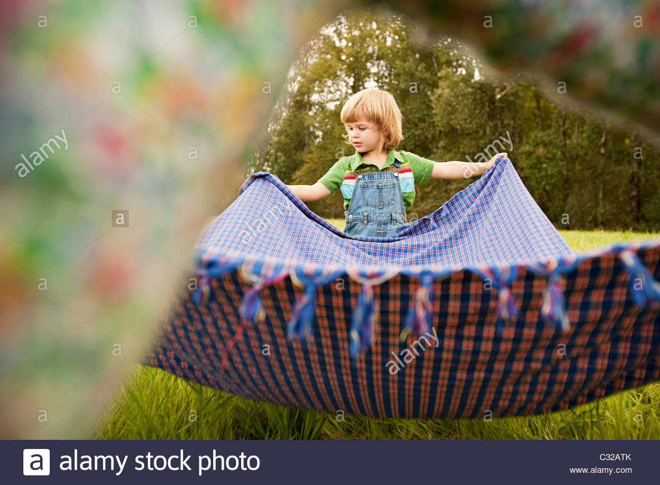 Boy in field with blanket - Stock Image