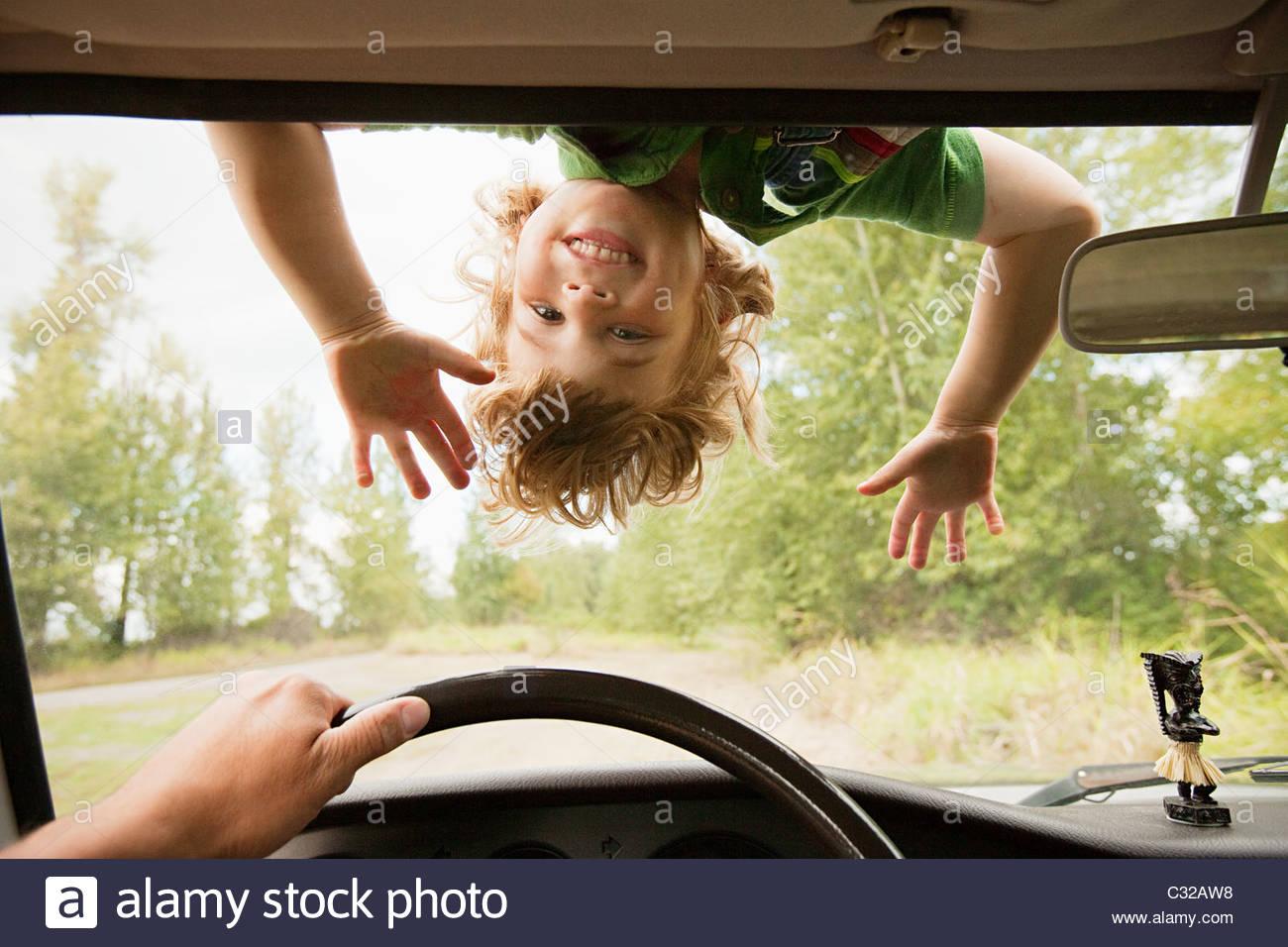 Boy upside down on car windscreen - Stock Image