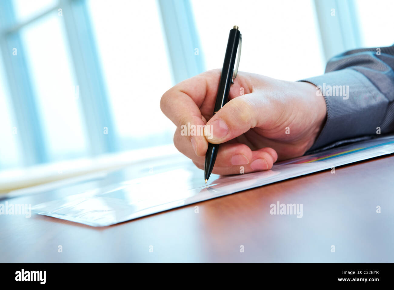 Close-up of male hand with pen making notes during conference - Stock Image