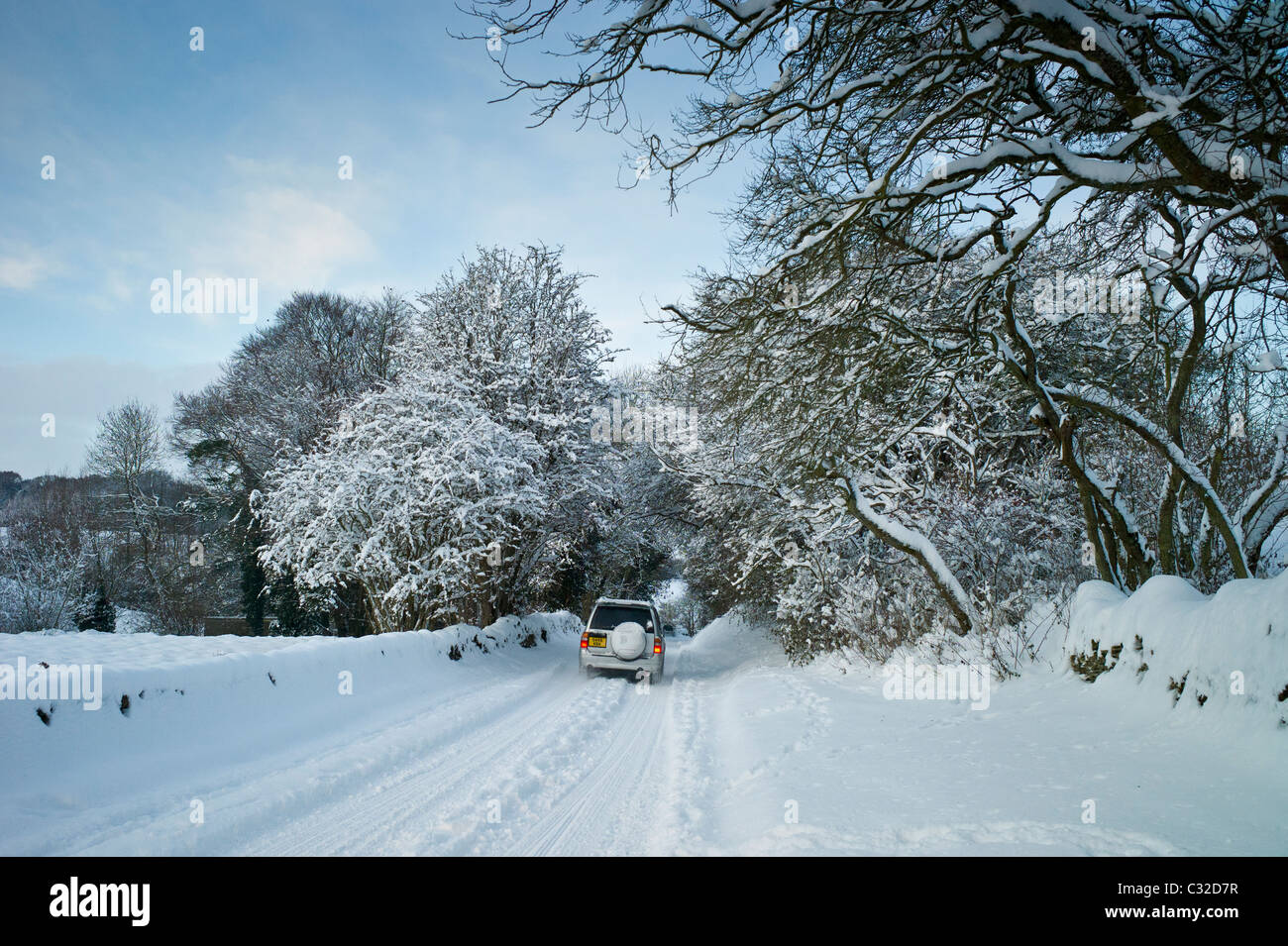 Four wheel drive vehicle in snow-covered lane in Swinbrook, The Cotswolds, UK - Stock Image