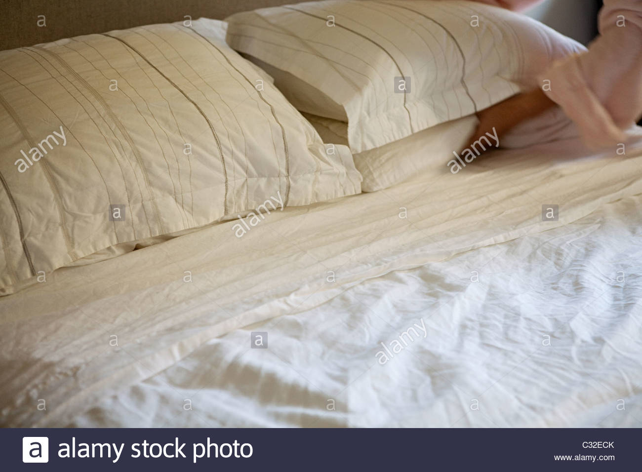 Woman making bed - Stock Image