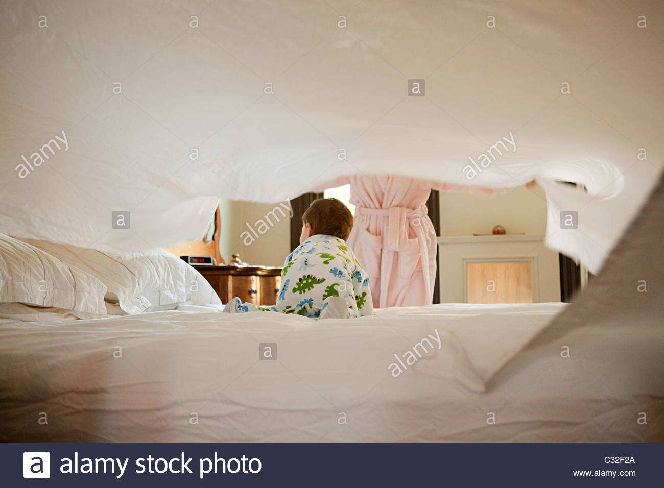 Mother and baby son making bed - Stock Image