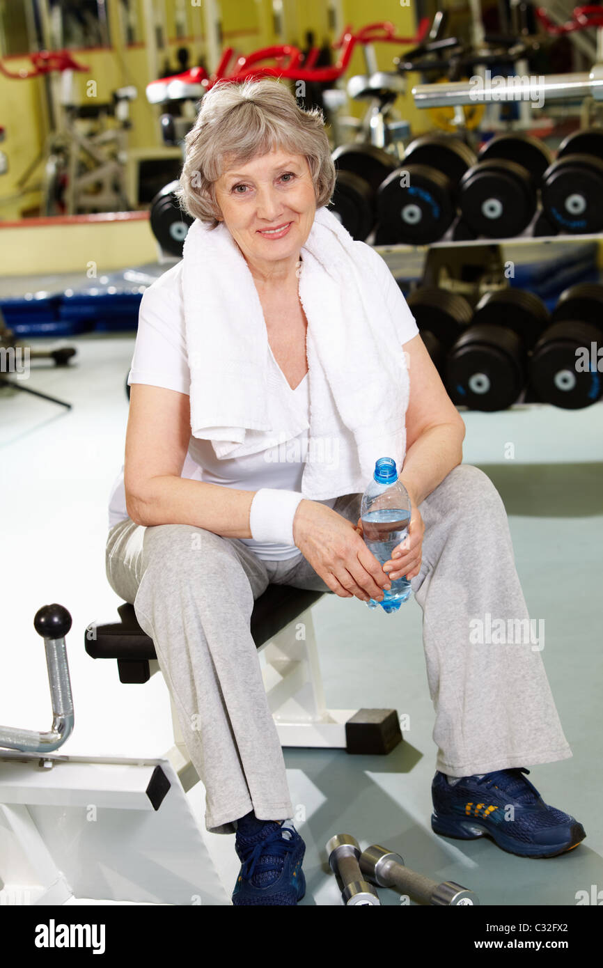 Portrait of aged woman with bottle of water in sport club - Stock Image