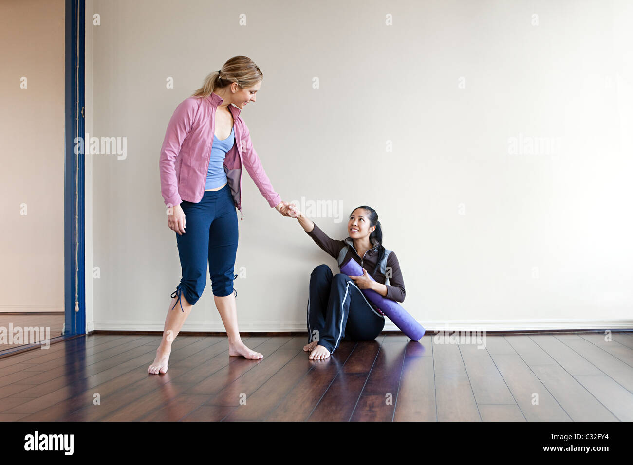 Woman helping another woman up from the gym floor - Stock Image