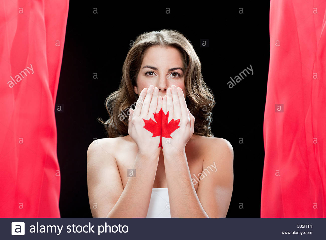 Woman with maple leaf painted on hands - Stock Image