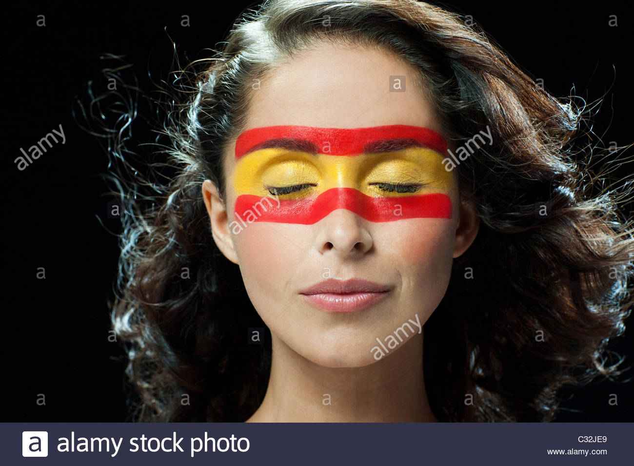 Woman with Spanish flag painted on face, eyes closed - Stock Image