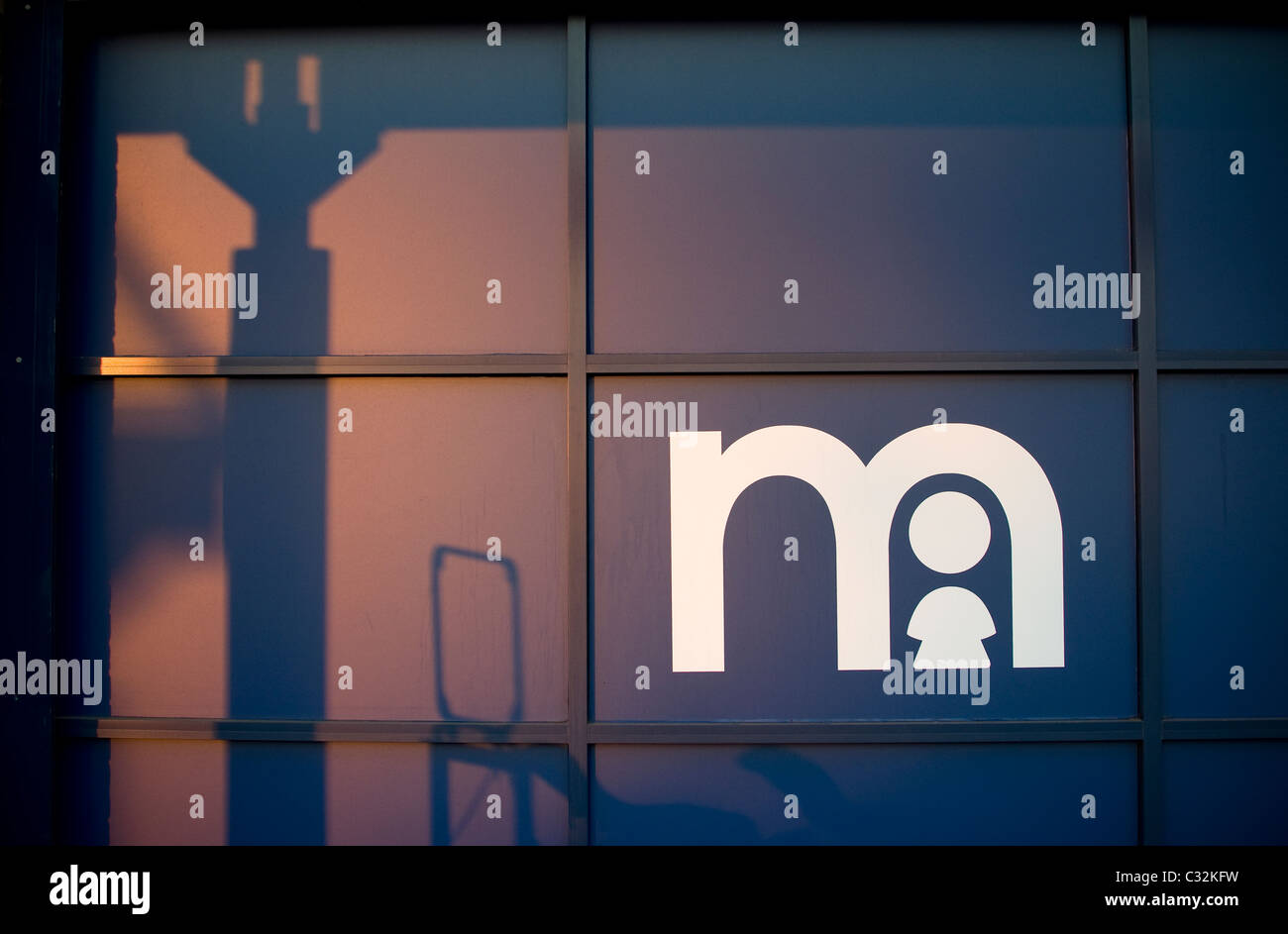 Mothercare sign, m, child, shadow, window, silhouette,mothercare, early, learning, centre, superstore, retail - Stock Image