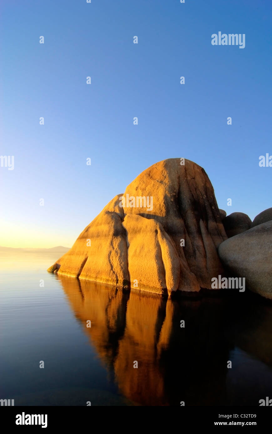 A large granite boulder is illuminated at sunset on the east shore of Lake Tahoe, NV. - Stock Image