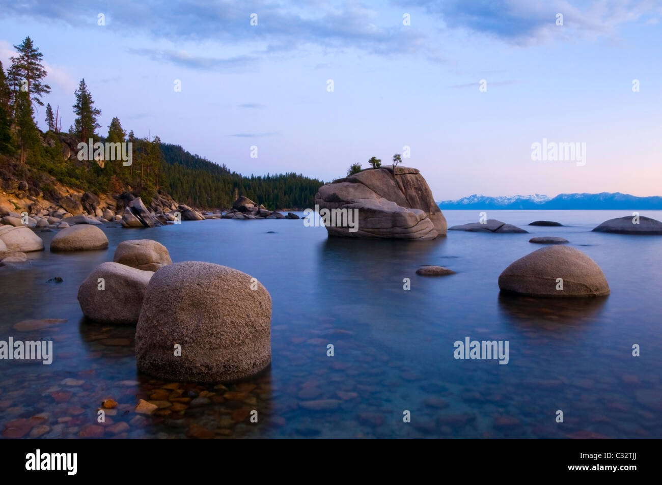 Evening light illuminates the granite boulders and calm waters of Lake Tahoe in the summer, NV. - Stock Image