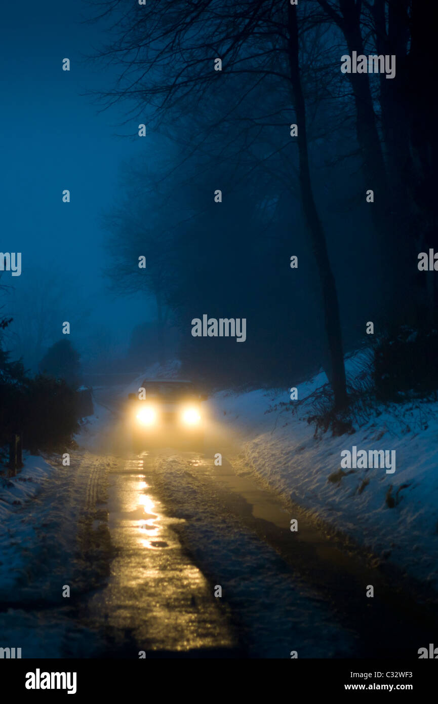 Car headlamps pierce the gloom on foggy day in The Cotswolds, UK - Stock Image