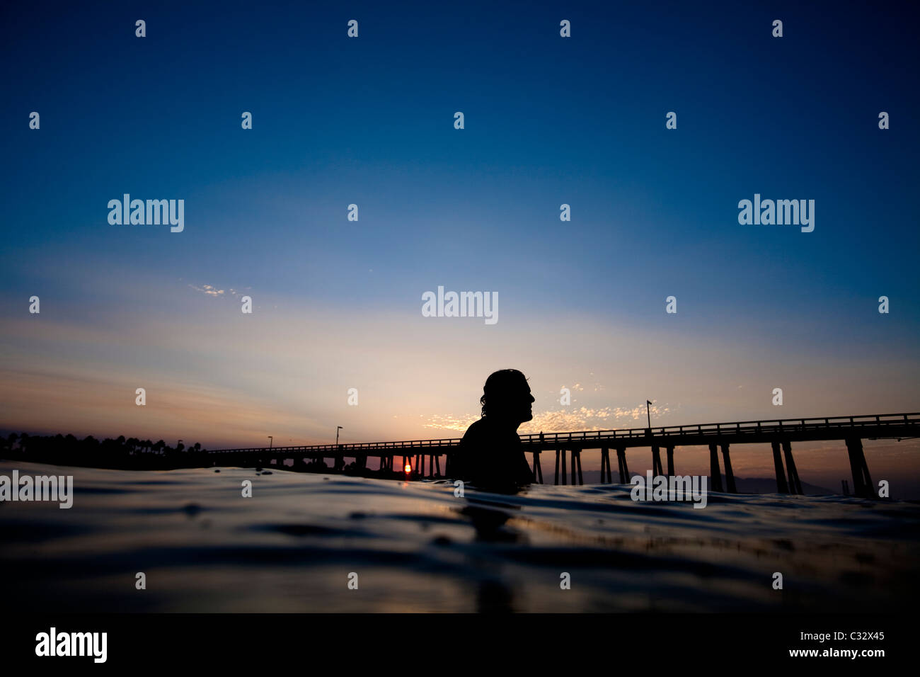 A male surfer watches the sunrise at Port Hueneme beach in Oxnard, California. - Stock Image