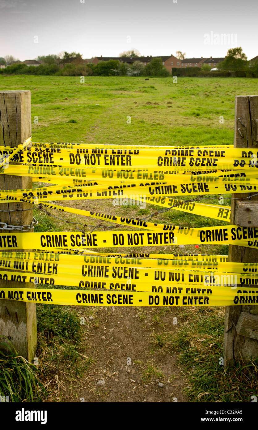 Yellow CRIME SCENE tape - Do not enter - between wooden posts with field in background. - Stock Image
