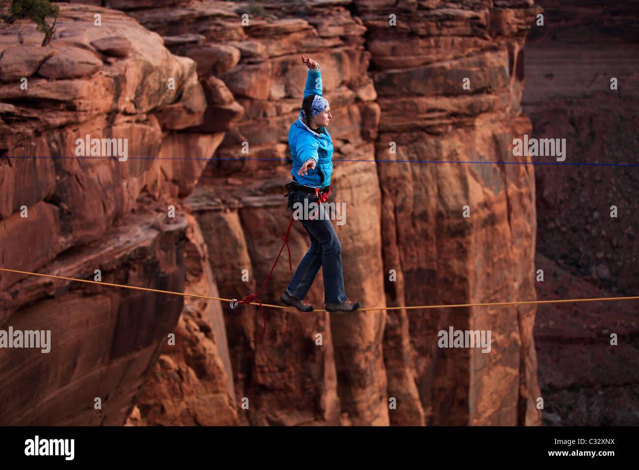 A female highliner walks across a highline at the Fruit Bowl in Moab, Utah, USA. - Stock Image