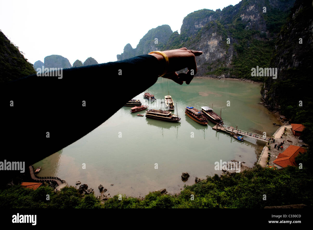 A climber points to limestone cliffs in Halong Bay, Vietnam.  Halong Bay has thousands of climbable limestone formations - Stock Image