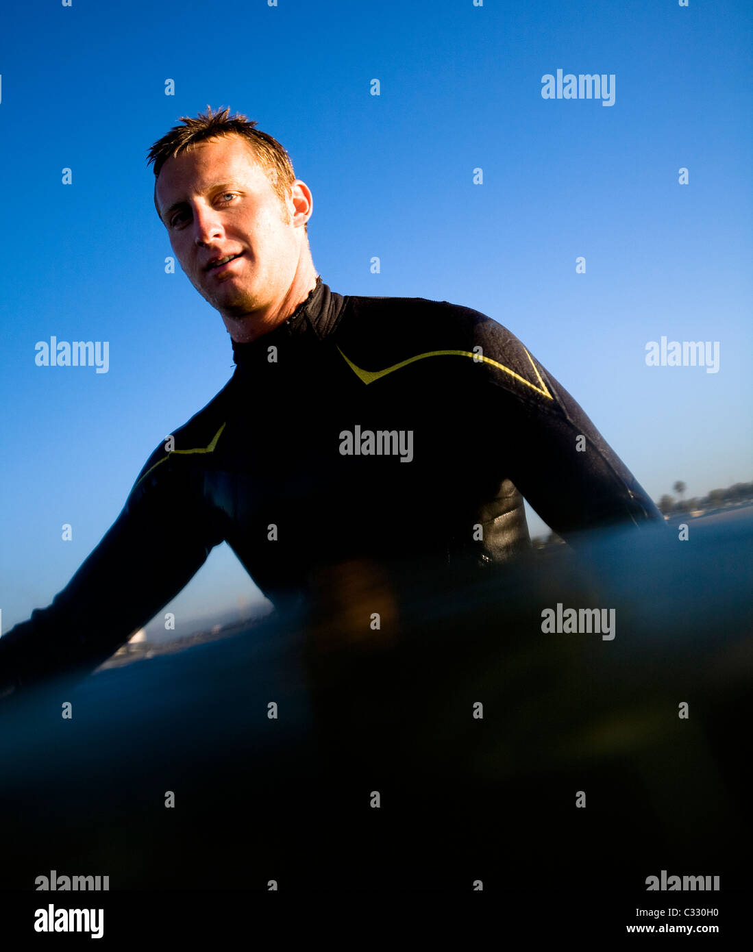 A young man in a wetsuit poses for a portrait while surfing at Port Hueneme, California. - Stock Image