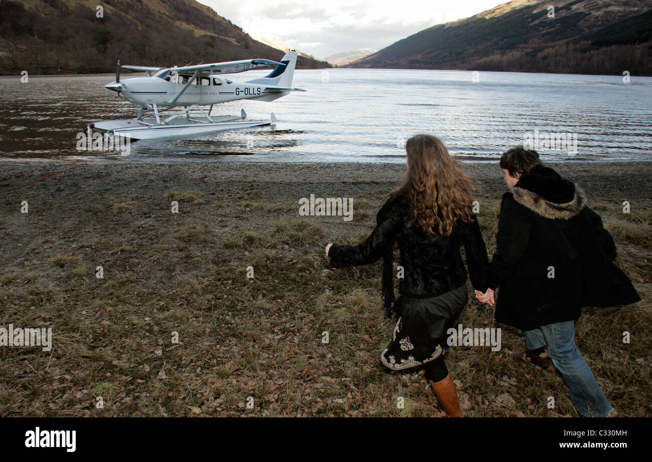 A young couple on a day trip to Loch Voil return to the Cessna seaplane which brought them there. - Stock Image
