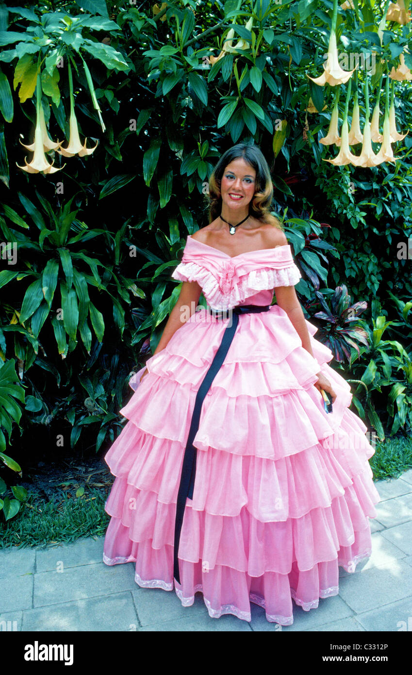 A pretty Southern Belle in a pink Antebellum gown greets visitors to ...
