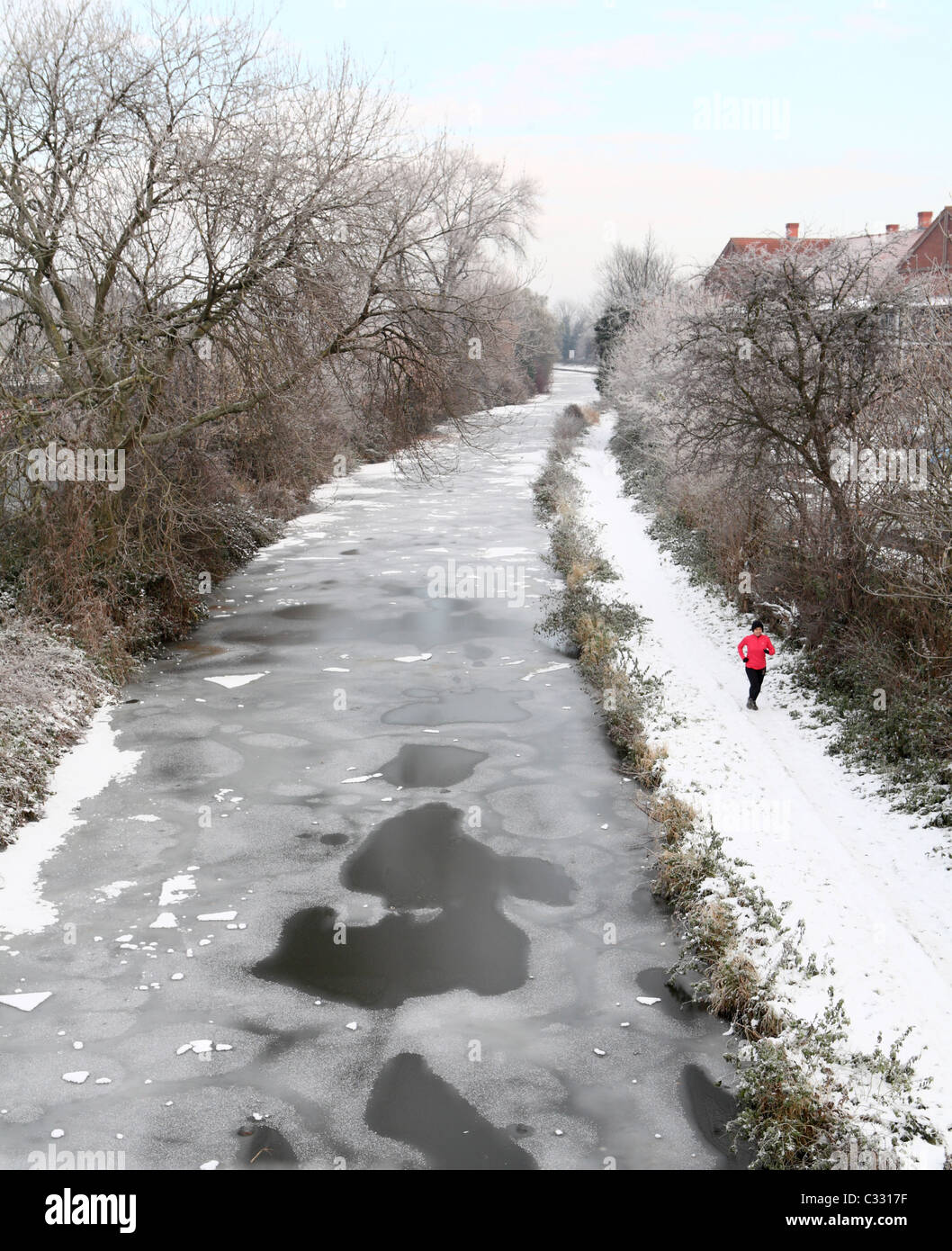 Frozen canal with runner - Stock Image