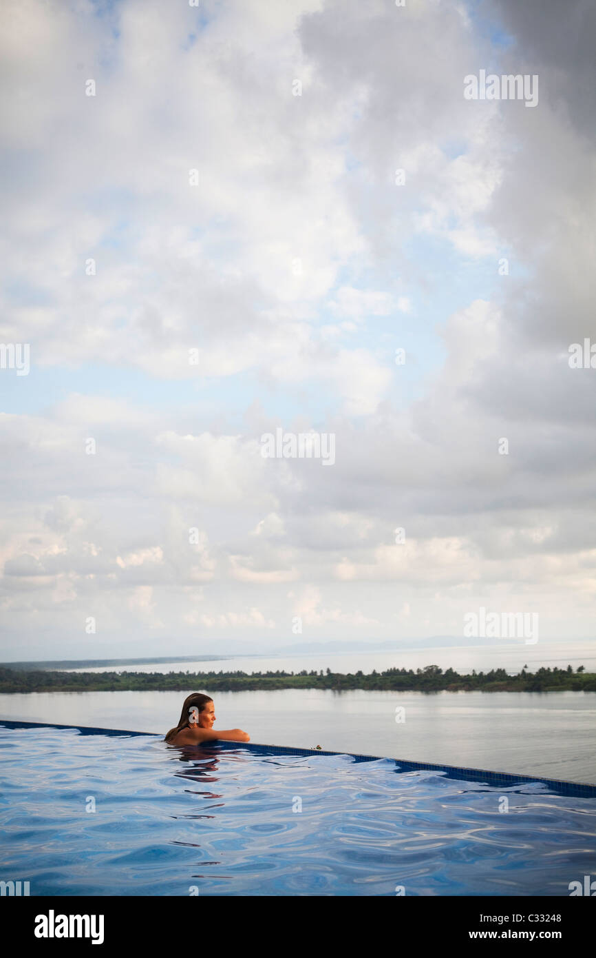 A woman sits with her arms on the edge of an infinity pool overlooking the wide open ocean. - Stock Image