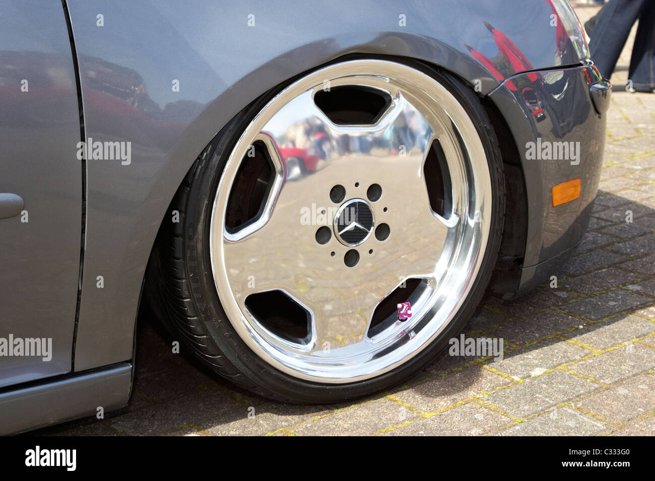 chrome mercedes wheel on a lowered suspension volkswagen golf with resultant wing damage at a modified car show Stock Photo