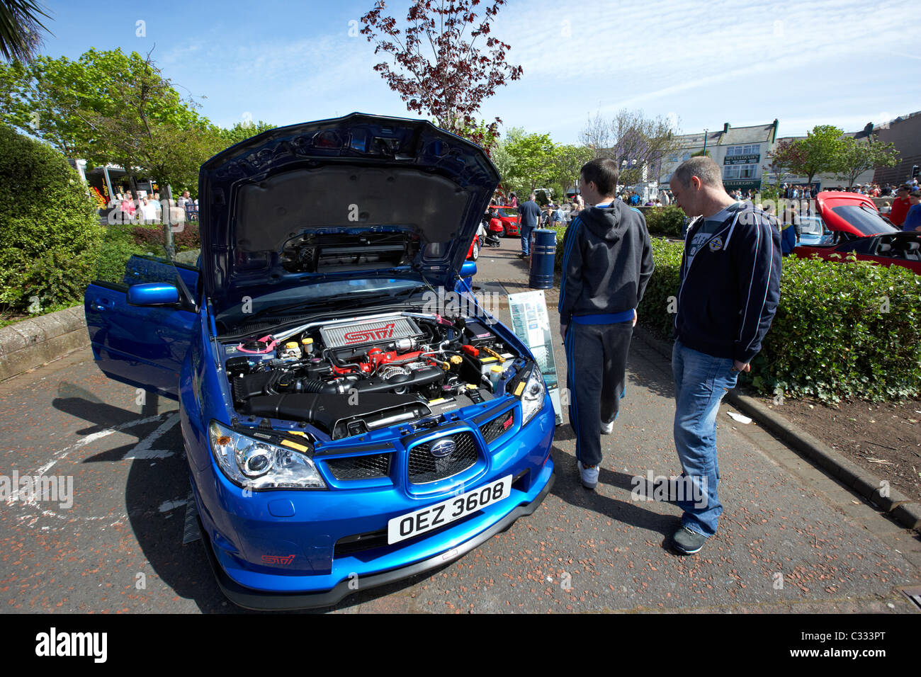 Two Men Walk Around A Subaru Impreza Wrx At A Modified Car Show In The Uk